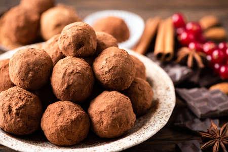 Homemade dark chocolate truffles on plate closeup view