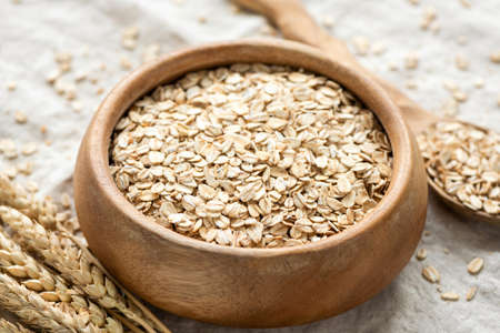 Dry oat flakes, oats, rolled oats in a wooden bowl. Concept of healthy eating, dieting, dietary fiber