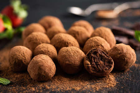 Homemade Dark Chocolate Truffles On Black Slate Background, Closeup View