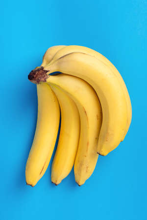 Fresh Bananas Isolated On Blue Background. Vertical Orientation 版權商用圖片