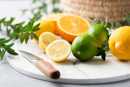 Fresh citrus fruits lemon orange and lime with leaf on marble board