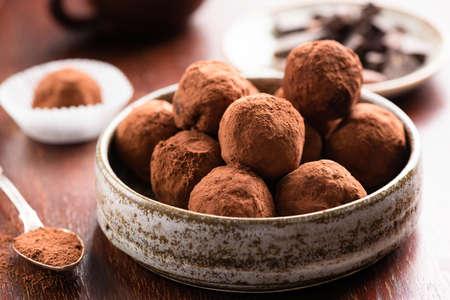 Homemade dark chocolate truffles on wooden background. Closeup view of chocolate candy truffle