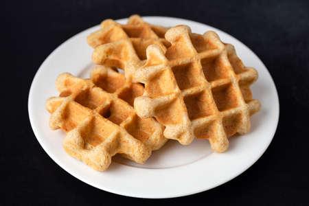 Homemade belgian waffles on plate, isolated on black background. Breakfast food sweet golden crunchy waffles 免版税图像