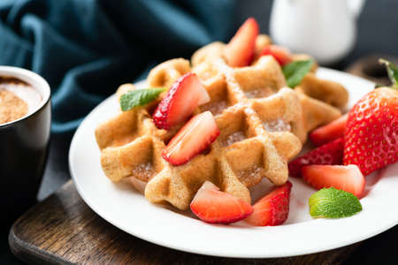 Belgian waffles with strawberries and confectionery sugar on white plate decorated with mint leaf. Closeup view. Tasty sweet breakfast food