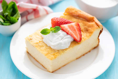 Tasty cottage cheese casserole with cream and strawberries on white plate. Homemade cheese cake perfect for breakfast or snack