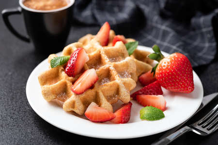 Belgian waffles with strawberries on white plate, black background. Sweet breakfast food 免版税图像