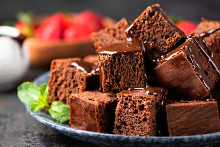 Chocolate cake or brownie cut in squares decorated with melted chocolate, closeup view. Homemade chocolate cakes