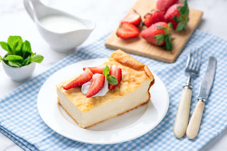 Cottage cheese casserole, zapekanka served with cream and strawberries. Healthy breakfast or snack cake rich in Protein and Calcium made of cottage cheese, tvorog