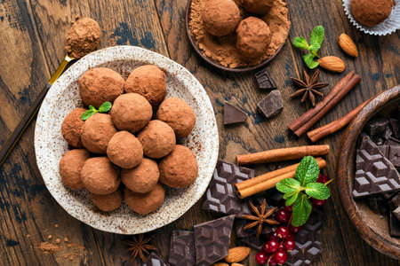 Homemade chocolate truffles with cinnamon on wooden table background, top view