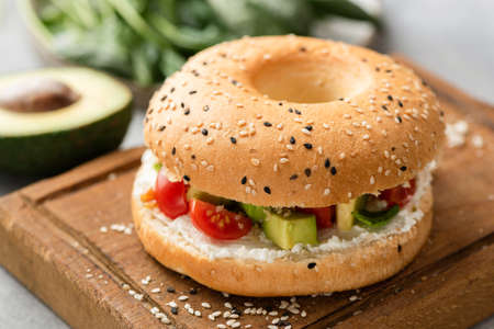 Bagel sandwich with cream cheese, avocado and tomato on wooden serving board, closeup view. Sesame bagel veggie burger