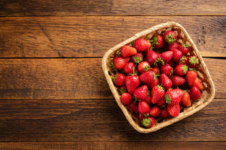 Strawberries in basket on wooden background. Top view, copy space for text Zdjęcie Seryjne