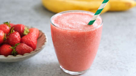 Strawberry smoothie in glass with green drinking straw. Fresh raw strawberry smoothie or summer cocktail