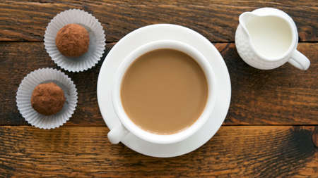 Coffee cup with cream and chocolate truffles on wooden table, top view