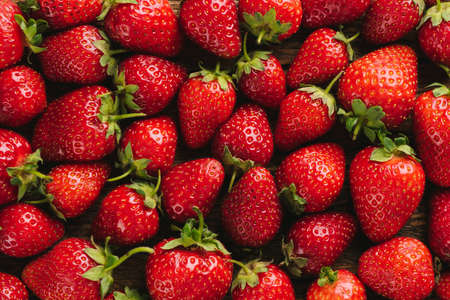 Strawberries as background. Freshly picked red strawberries. Fruit wallpaper
