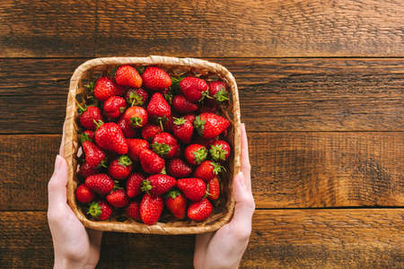 Freshly picked strawberries in basket in female hands. Top view, wooden table background, rustic style