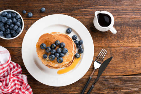 Pancakes with blueberries and honey on a wooden table. Top view copy space