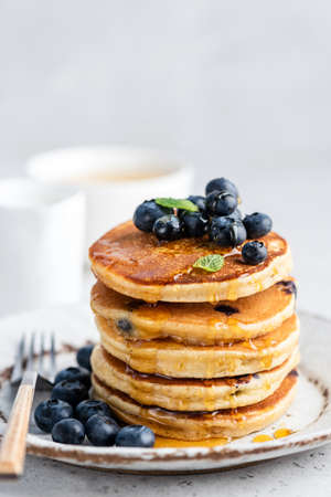 Blueberry pancakes with honey on plate. Stack of fluffy pancakes. Tasty sweet breakfast food