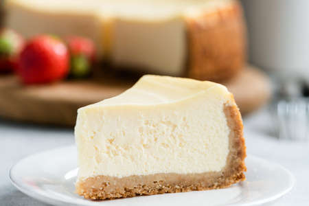 Slice of classic new york cheesecake on white plate, closeup view