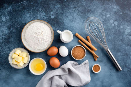 Baking ingredients for making cake, pastry or sweet bread on textured blue background. Cooking ingredients top view Banque d'images