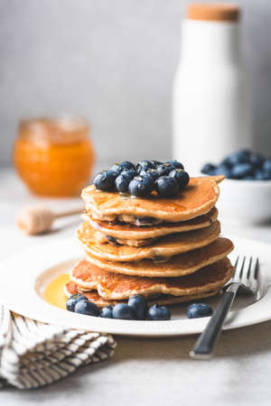 Pancakes with blueberries and honey on a plate. Tasty pancakes. Toned image Фото со стока