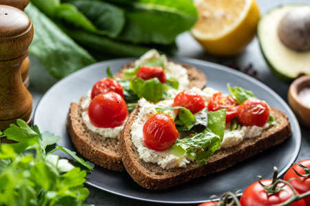 Tasty sandwich with soft white ricotta cheese, roasted tomatoes and basil garnished with crushed pepper and olive oil Banque d'images