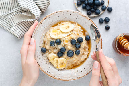 Oatmeal porridge with banana, blueberries and honey. Female hands holding bowl of oatmeal porridge over grey concrete background, table top view