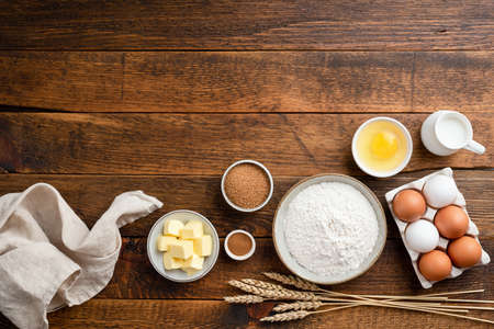 Ingredients for baking on a rustic wooden background. Flour, eggs, butter, sugar and other ingredients for baking a cake, sweet bread pastry or cookies