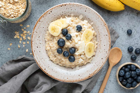 Healthy breakfast porridge oatmeal with banana, blueberry, coconut. Top view, concrete background
