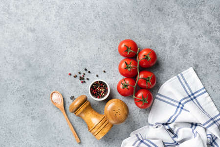 Tomatoes and spices for cooking on grey concrete background. Fresh cooking ingredients. Recipe, food background, menu concept Banque d'images