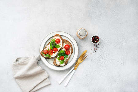 Italian food, bruschetta with ricotta cheese, basil and tomato on plate. Top view Banque d'images