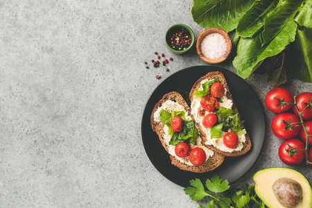 Healthy vegetarian bruschetta or toast with roasted tomatoes and ricotta cheese on a black plate, top view, copy space. Italian food concept Banque d'images