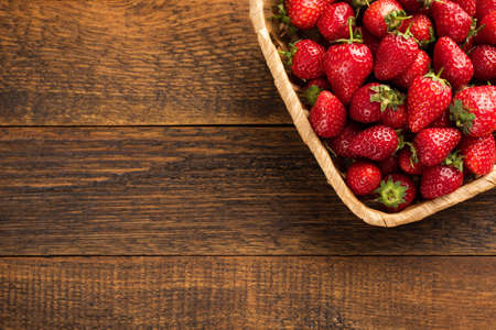 Fresh strawberries in basket on a wooden table, top view with copy space. Organic strawberries harvest