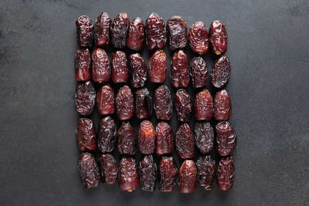 Dry Medjool Dates On Black Slate Background. Group of Dried Date Fruits. Arabic Food