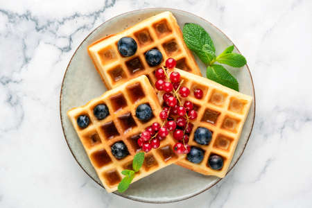 Square belgian waffles with berries on a plate isolated on marble background. Top view. Sweet waffles