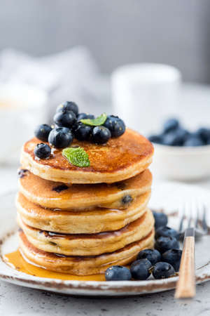 Blueberry pancakes stack poured with flower honey. Tasty breakfast pancakes with blueberries