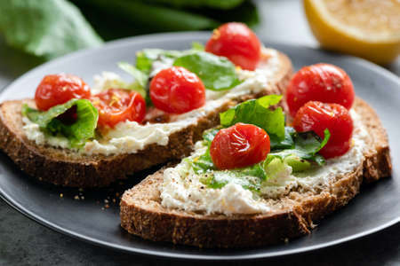 Toast with soft ricotta cheese, roasted tomatoes and lettuce garnished with olive oil and black pepper. Healthy gourmet italian bruschetta