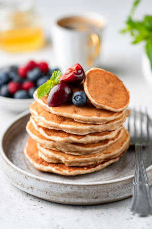 Vegan oat pancakes with berries on plate. Gluten free pancakes stack