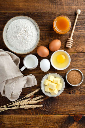 Ingredients for baking on a wooden table background. Flour eggs sugar butter and honey. Vertical orientation, rustic food photo. Flat lay kitchen food ingredients