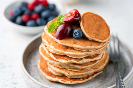 Healthy oat pancakes with berries on a plate. Vegan gluten free pancakes Banque d'images