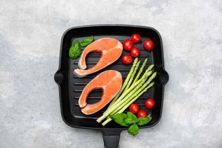 Salmon steaks with asparagus, tomatoes and basil on a pan. Isolated on grey concrete background. Healthy food Banque d'images