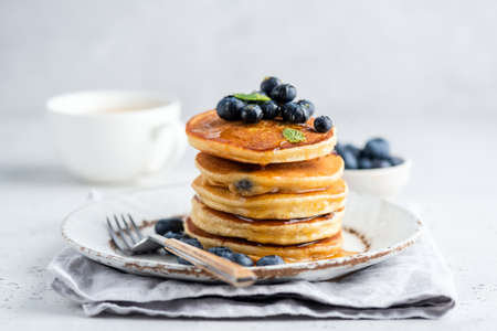 Tasty pancakes with blueberries and honey on a plate. Grey background Banque d'images