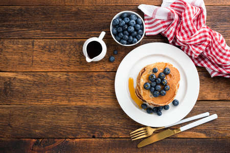 Pancakes with blueberries and maple syrup on wooden table background. Table top view, copy space