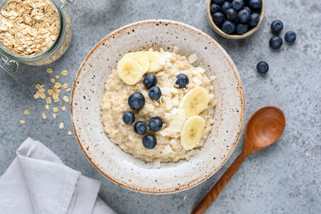 Oatmeal porridge bowl with banana, blueberries, coconut on concrete background, top view