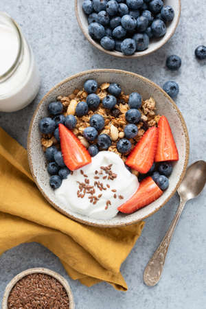Granola bowl with berries and yogurt on concrete background. Healthy breakfast food top view vertical orientation