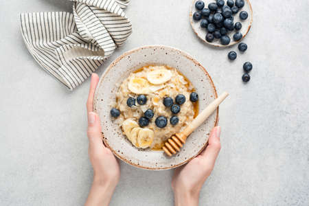 Female hands holding bowl of oatmeal porridge with banana slices, blueberries, coconut flakes and natural raw honey over grey concrete background, table top view. Concept of healthy food