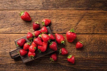 Organic strawberries on wooden table. Fresh summer berry harvest, eco berries Stock fotó