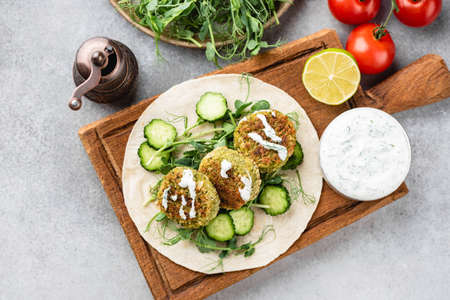 Vegan falafel with vegetables and tzatziki sauce on wooden board, top view. Arabic food