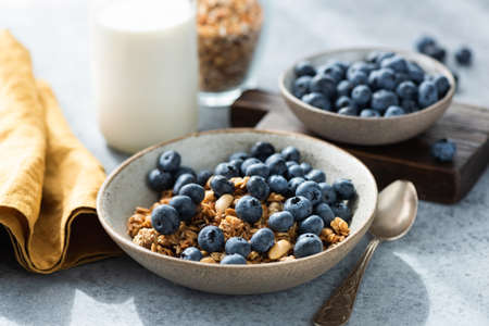 Bowl of granola with blueberries and bottle of milk. Healthy breakfast food Banque d'images