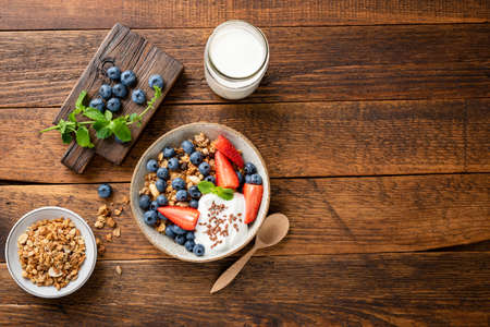 Oat granola with greek yogurt and summer berries in a bowl. Top view on a rustic wooden table background, copy space. Nutrition, healthy eating concept