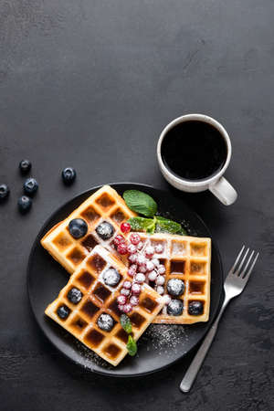 Square belgian waffles with berries and icing sugar and cup of black coffee on black concrete background. Top view copy space for text or design